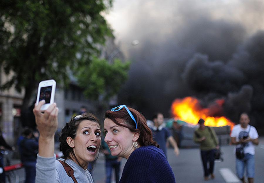 Obra sense títol de Manu Fernández (AP Photo), continguda en l'exposició Fragments. Turistes s'autoretraten mentre els manifestants cremen un contenidor de fem durant les protestes de Barcelona, dimarts 1 de maig del 2014.