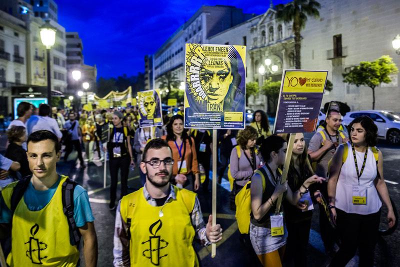 Activistes d'Amnistia Internacional en la manifestació realitzada entre la Facultat de Medicina i Odontologia i la plaça del Patriarca. Foto: Miguel Lorenzo.